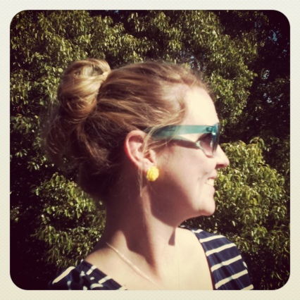 blonde topknot teal sunglasses yellow flower studs