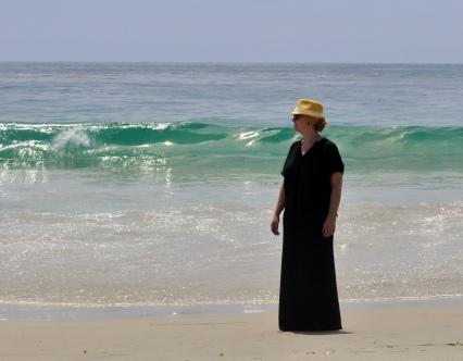 yellow fedora black maxi black dress at beach