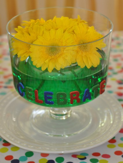 rainbow kids birthday party triful bowl with yellow daisies and green colored water celebrate glitter adhesive letters