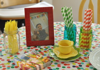 rainbow kids birthday party tablescape red photo frame mason jars striped straws